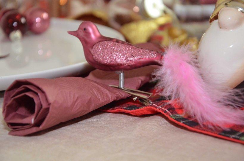Weihnachtsbaumschmuck ein Marsala farbender Vogel mit Federn der als Serviettenhalter dient.